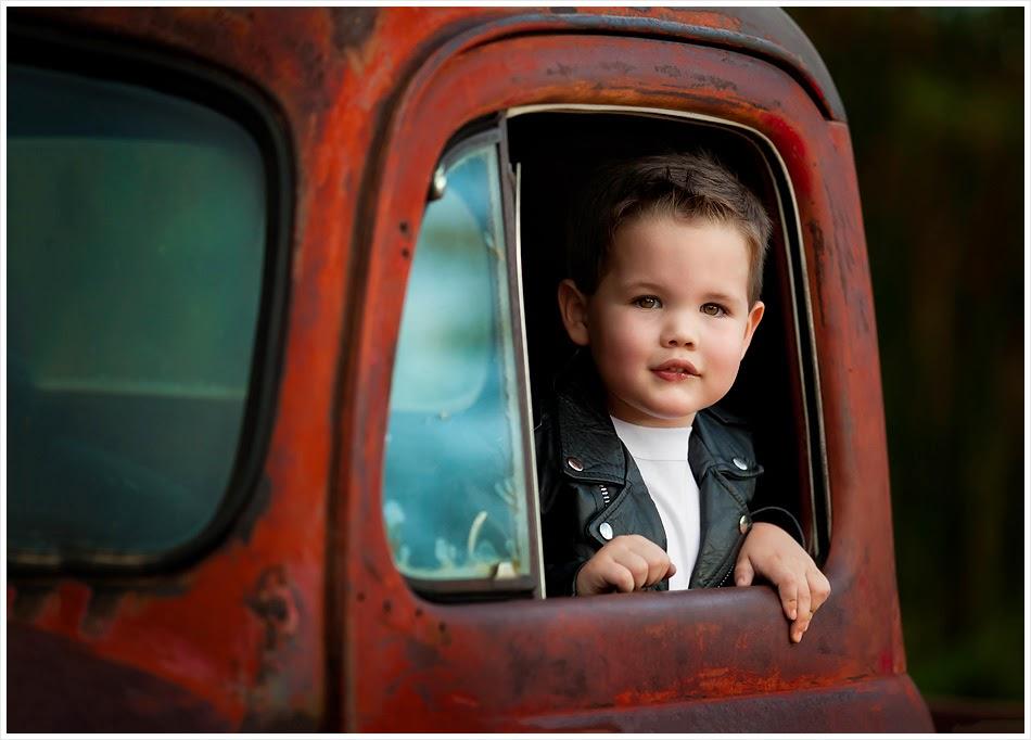 photo de Lisa Holloway représentant une jeune garçon en blouson de cuir noir à travers la fenêtre d'un vieux pick up rouillé
