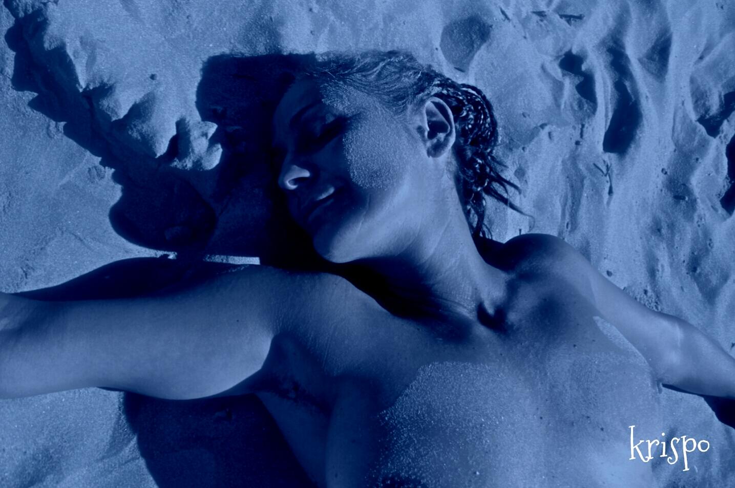 detalle del torso de una mujer tumbada en la playa de noche
