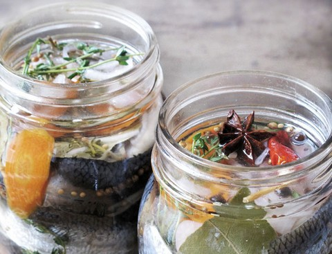 Pickled herring with whole spices in a jar