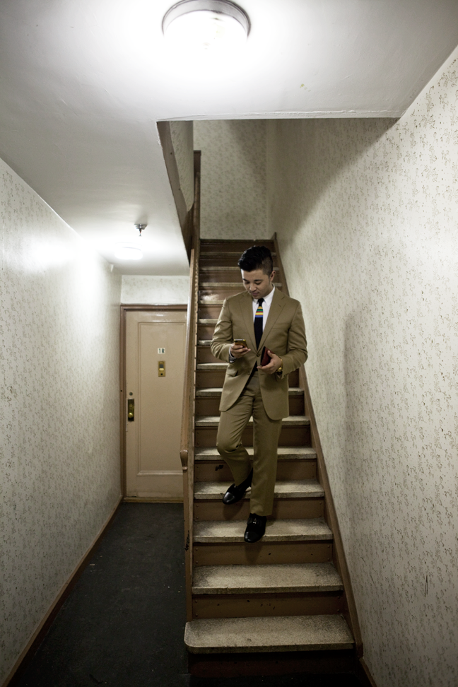 Danlly shot in his apt complex dressed in a tan Burberry suit Prada tie