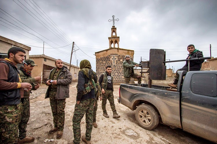Kurdish fighters in front of a church in the village of Tel Jumaa on Wednesday (Reuters).