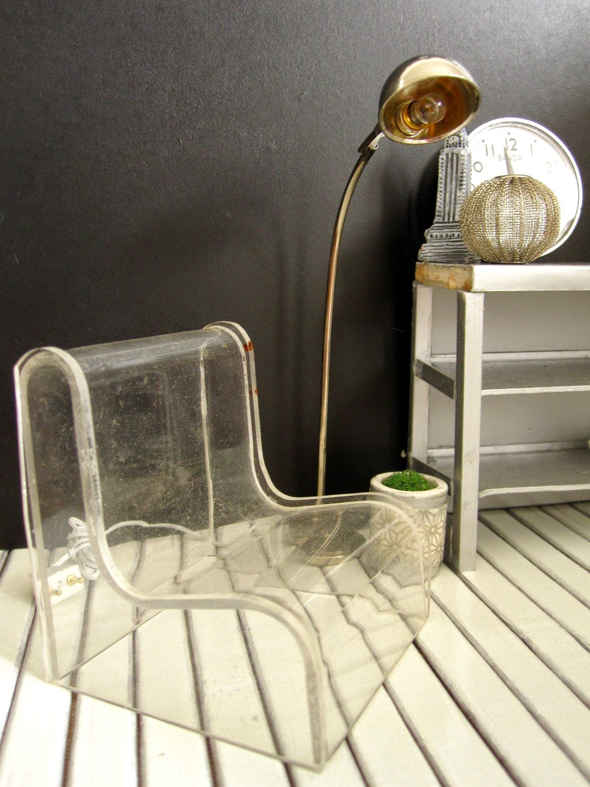 Corner of a modern dolls' house miniature interiors shop, with a clear perspex lounge chair, a silver floor lamp and a grey industrial bench on display.