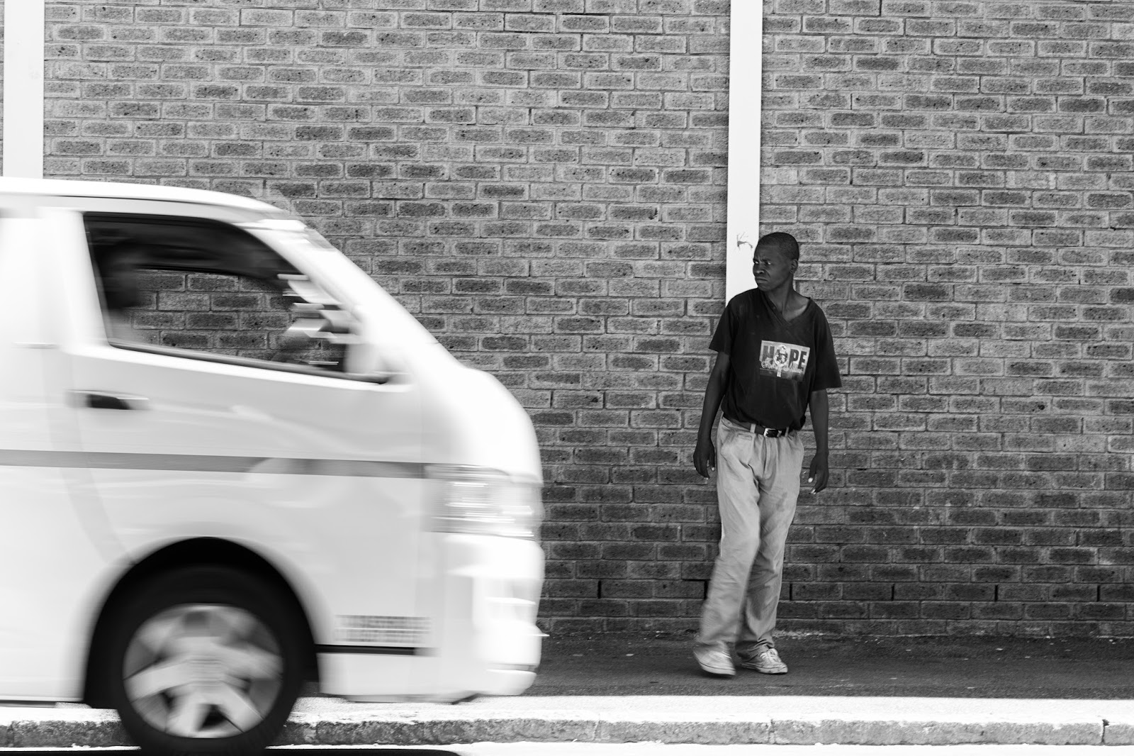 A man waits for a taxi to stop and pick him up - Salt River Cape Town