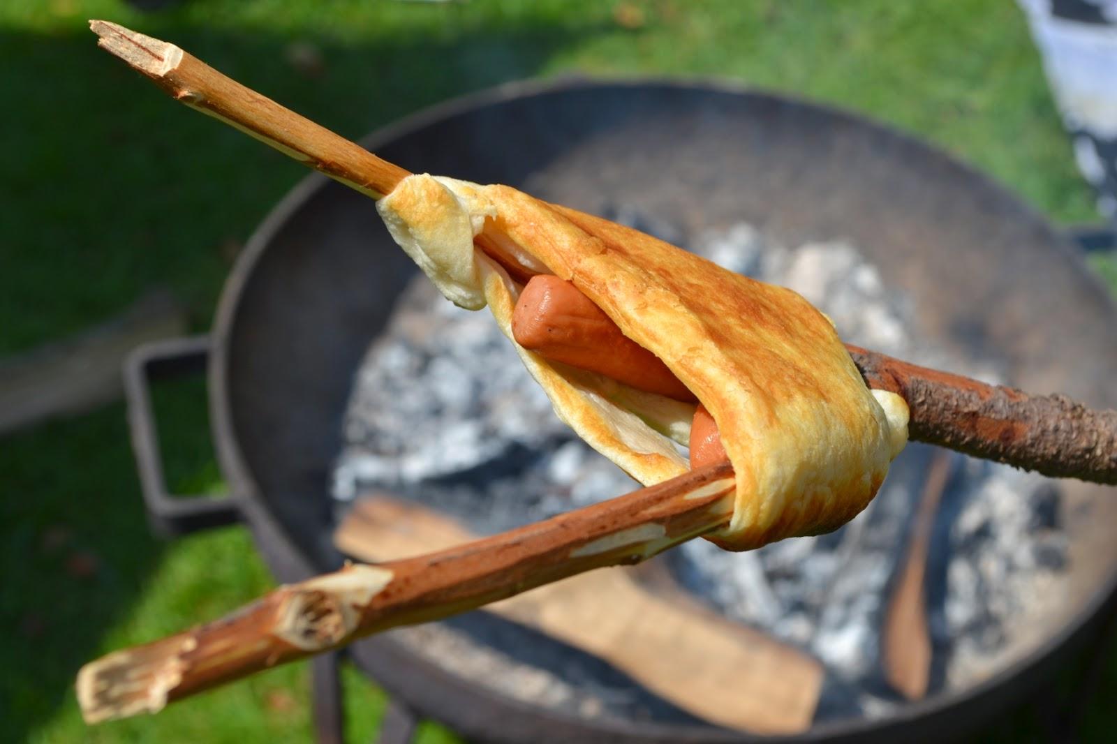 Vorkstok met gebakken croissantdeeg en een knakworst erin boven een bak hete houtskool