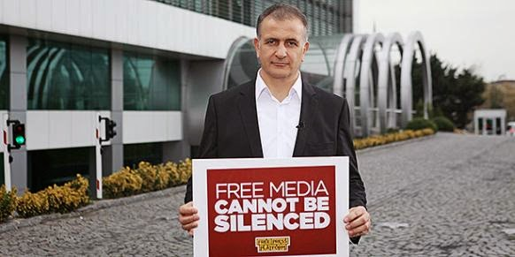 Zaman Editor-in-Chief Ekrem Dumanli poses with sign that reads 'Free media cannot be silenced'