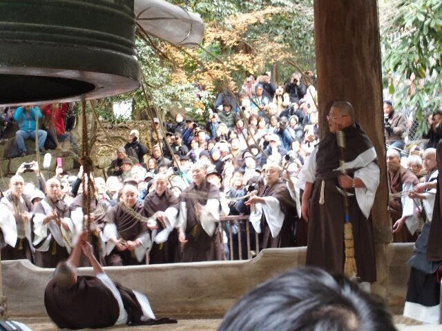 親綱1人を持つ僧が仰向けになり反り返るようにして地面スレスレに力強く鐘をついた。