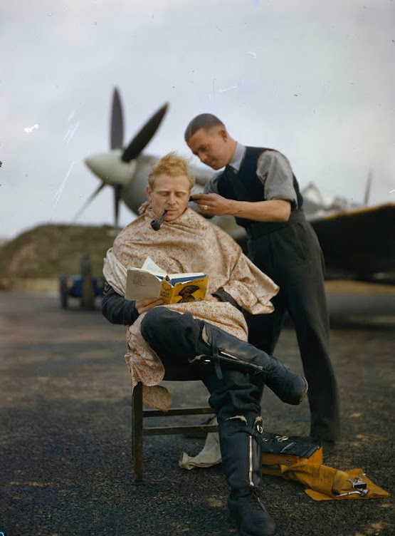 An RAF pilot getting a haircut while reading a book between missions during World War II.