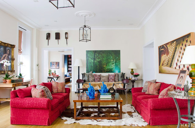 Apartment living room with red dueling sofas, an animal skin rug, a wooden coffee table, high ceilings and two pendant lights