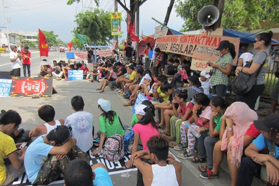 Striking workers hold program at the picket line with their families and supporters. Photo Credits: Kilusang Mayo Uno.