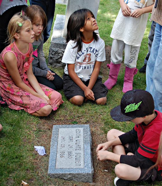 children gather around Edith Bowen's headstone