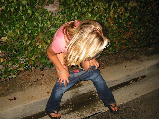 Drunk college girl pissing on the sidewalk in public.