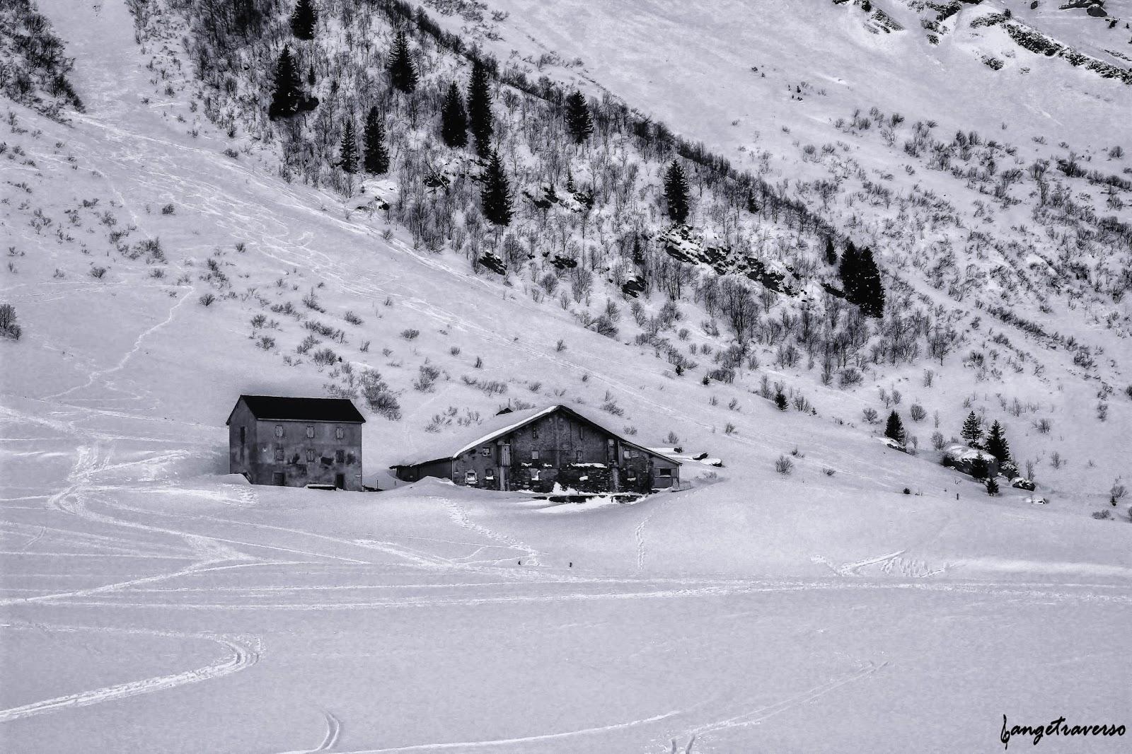 Massif des Aravis, photo de chalets de montagne dans la neige prise depuis le col des Aravis