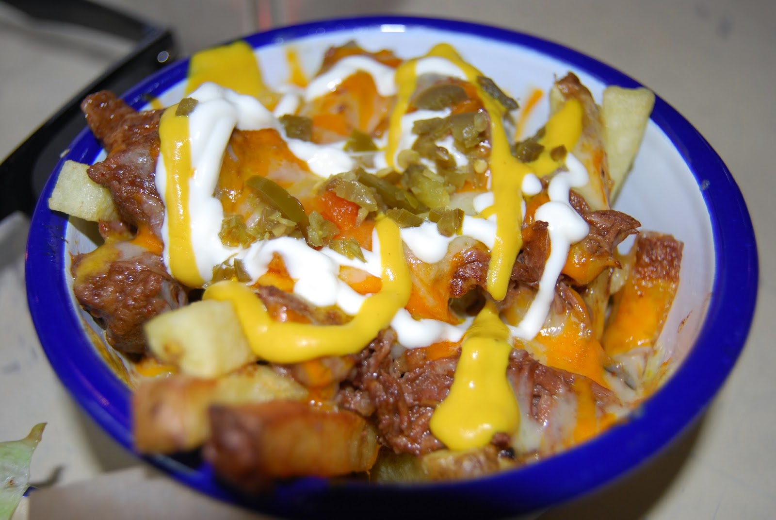 fries, pulled beef, sour cream, jalapeno
