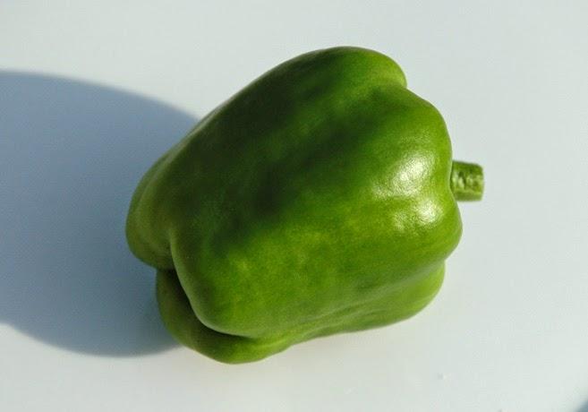 En grön paprika mot vit bakgrund