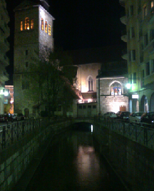 Canal at night in Annecy, stone buildings lit up