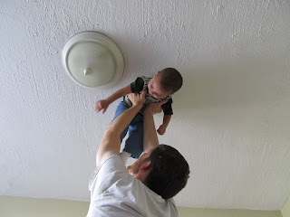 Hubby holding Bean to the ceiling