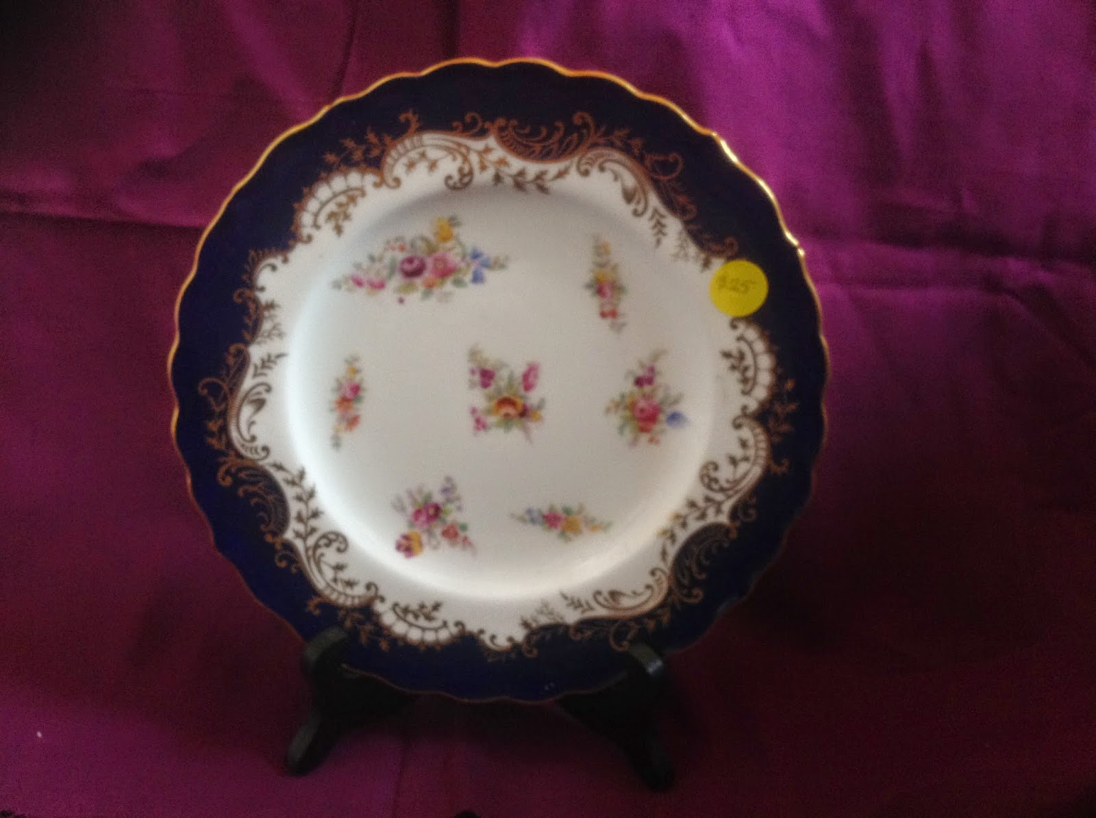 small white china plate with floral centre and blue and gold edge