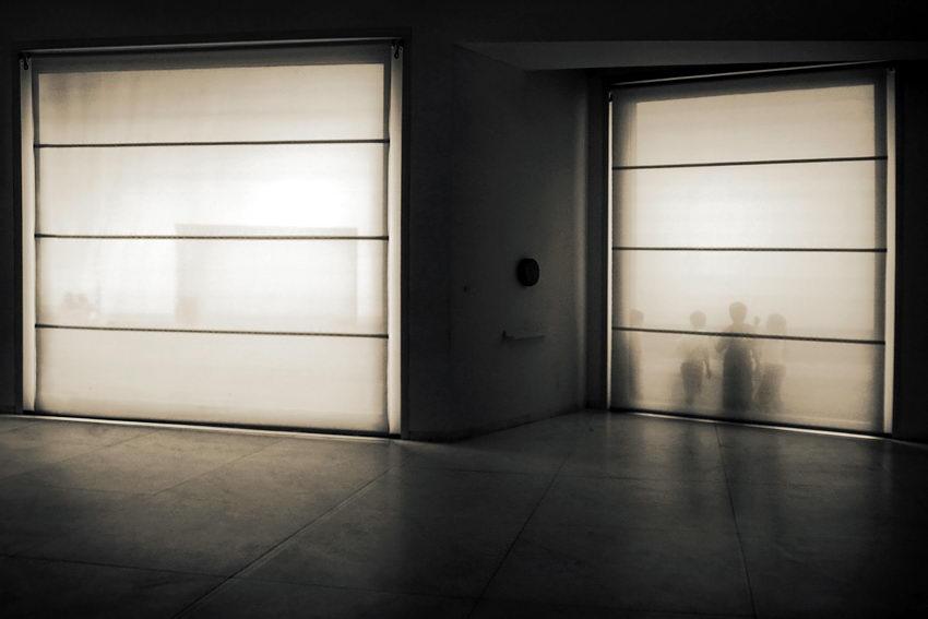 Duas janelas até ao chão com cortinas translúcidas, de forma que se percebem vultos de pessoas na rua, através delas