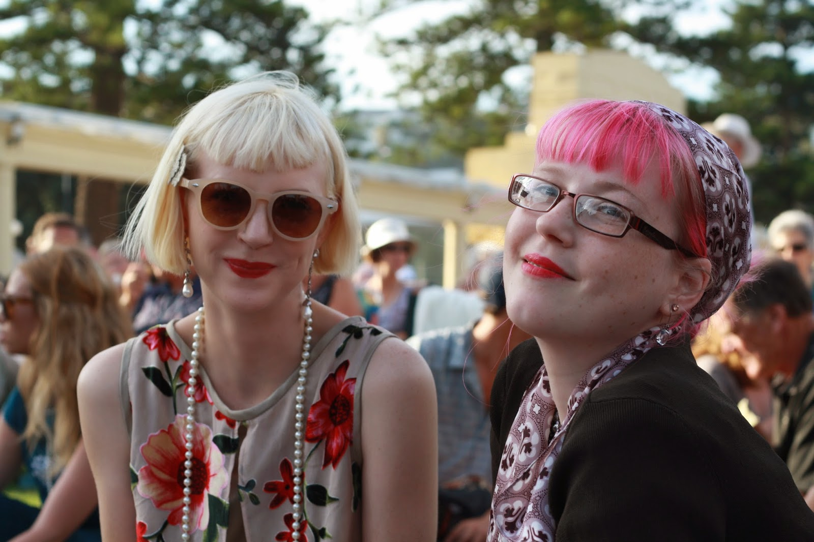 A girl with a blonde, art deco bob and pearls, smiling. Another girl with pink hair and a smile.