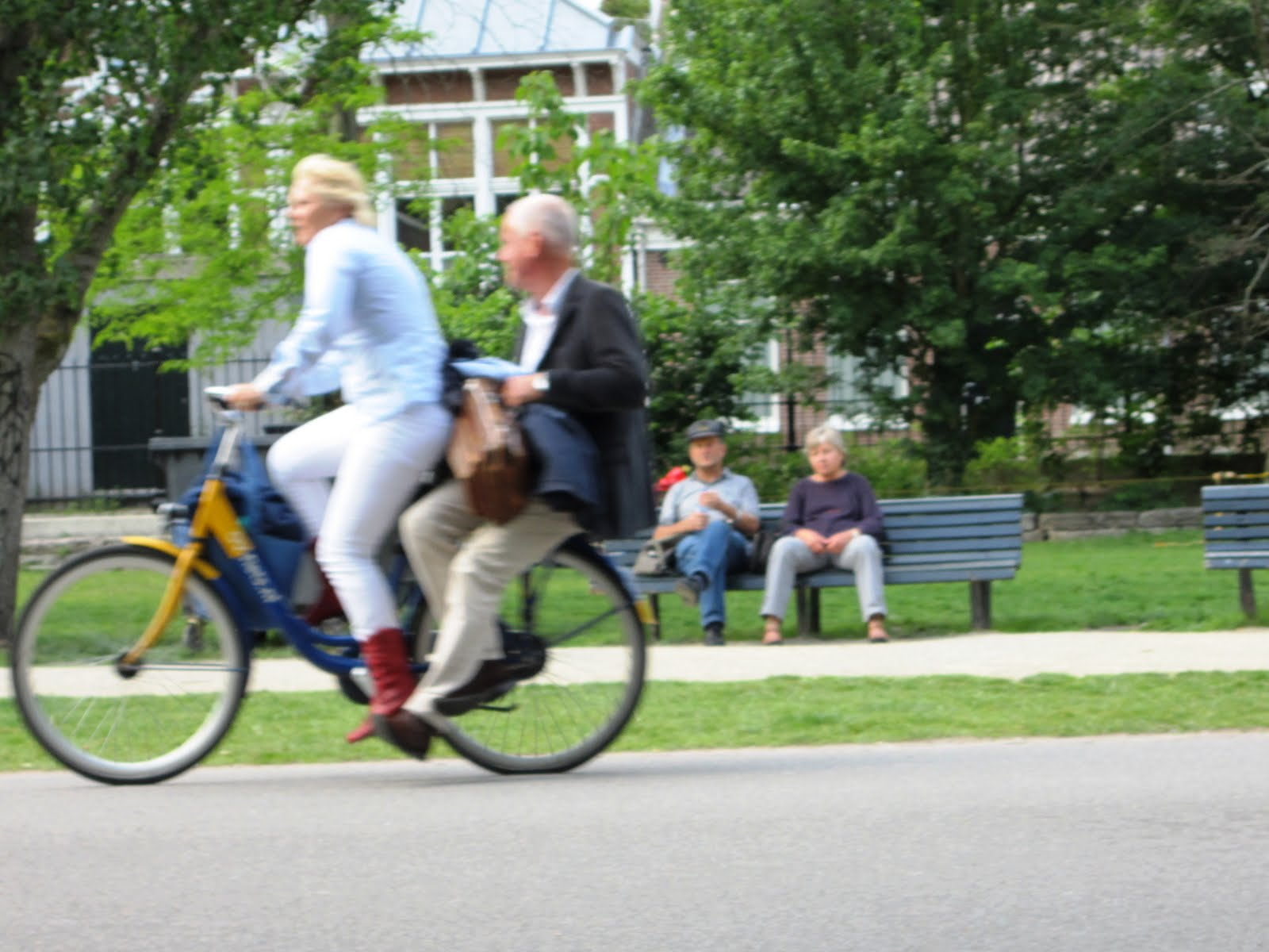 The woman is pedaling along and the well-dressed man is enjoying the ride.