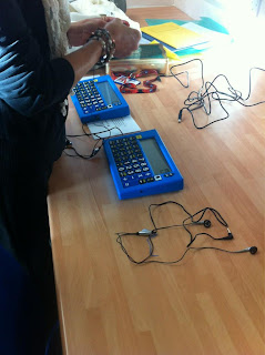 Two Identicle blue calculators on a desk with a woman's hand unravelling new headphones to try in them.