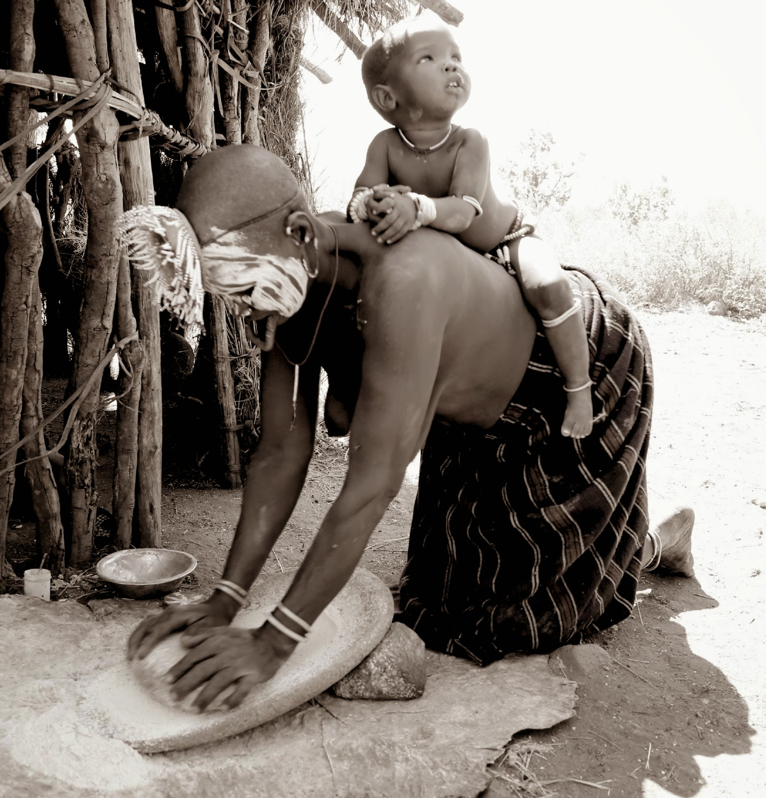 Mursi woman grinding sorghum on a grinding stone with child on back