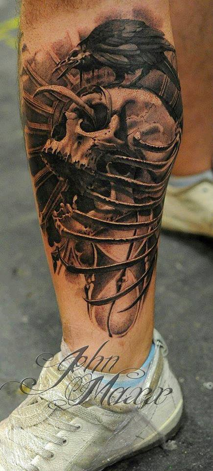 Black ink skull and crow tattoo on leg