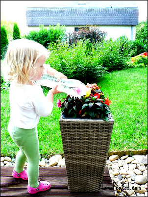 toddler watering garden with a DIY watering can