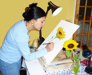 Neelam standing in front of an easel with a partly-completed image of a sunflower.  The real sunflower is besider her.