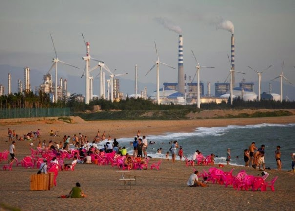 Windmills and a power plant are seen in the distance as beachgoers watch sunset in the city of Dongfang on the west side of China's island province of Hainan, June 18, 2014.  (Credit: Reuters/John Ruwitch) Click to enlarge.