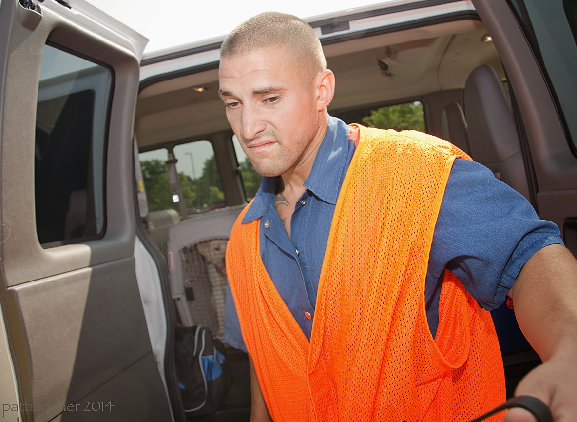 The man wearing the blue prison uniform and an orange vest is turning away from the van. He is looking down facing the camera with a strained expression on his face.