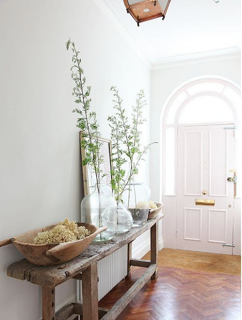 foyer in a UK country house with reclaimed wood table, gray walls, and walnut herringbone wood floors