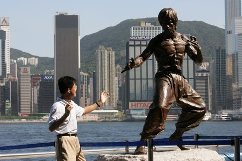 Tourist pose like Bruce Lee statue for picture at the Avenue of Stars, today is the 33rd anniversary of the death of Bruce Lee. 20 July 2006
