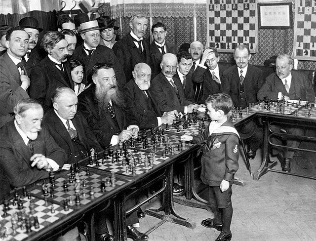 Niño genio jugando ajedrez contra personas adultas