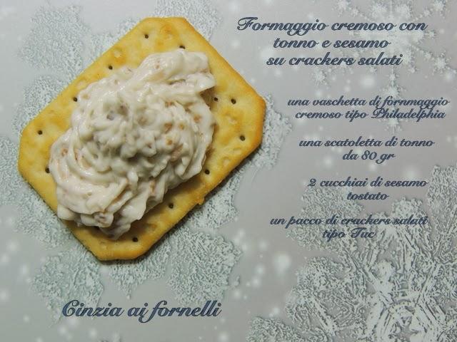 aperitivo con crackers salati, formaggio e sesamo tostato