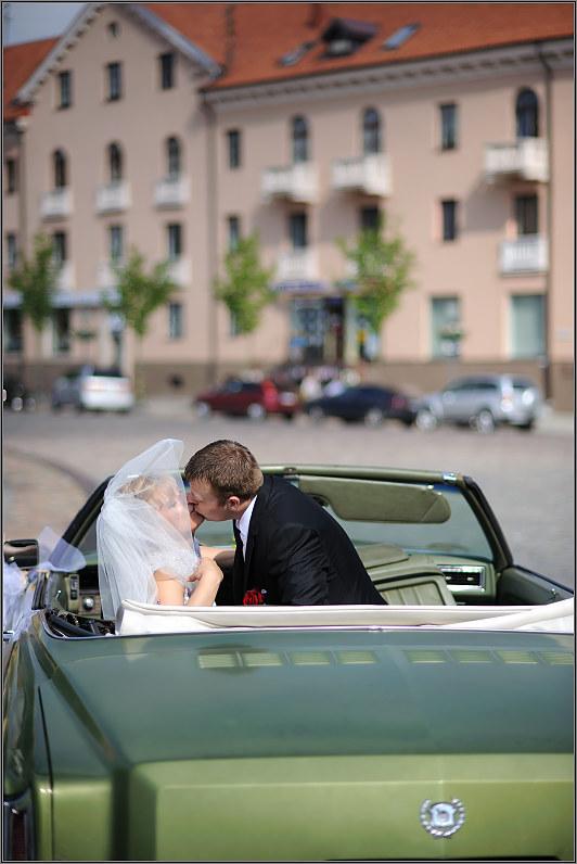 romantiškas jaunavedžių bučinys automobilyje