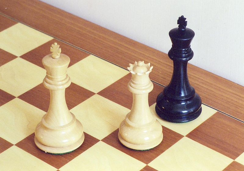 A white king and queen putting a black king into checkmate