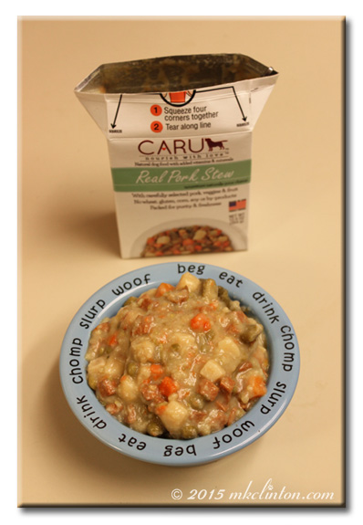 Blue dog bowl filled with Caru Real Pork Stew and empty container