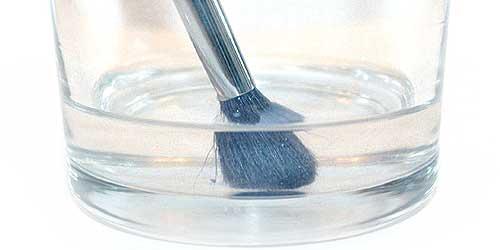 vaso con alcohol para desinfectar pincel de maquillaje