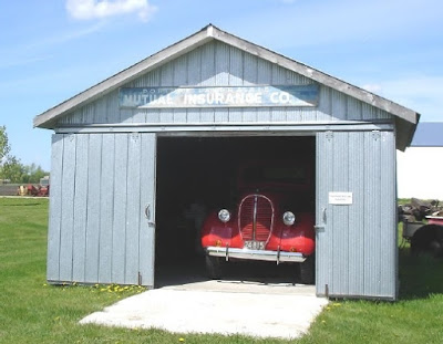 Metal shed with red truck inside
