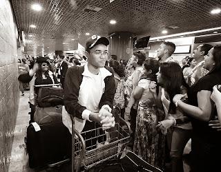 Estudantes em fila empurrando seus carrinhos com malas em um aeroporto, cercados por uma grande quantidade de pessoas paradas em postura de expectativa.