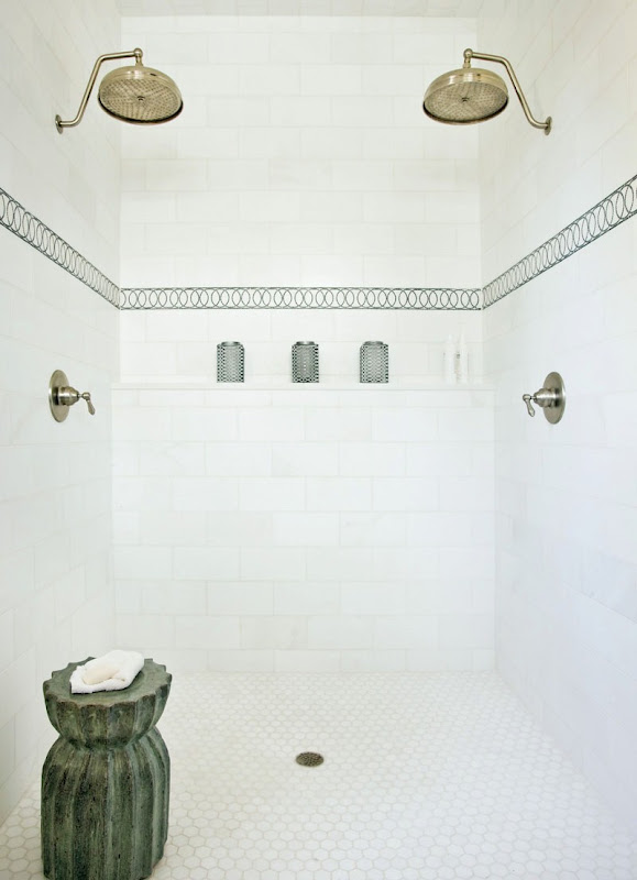 Shower white tile tile on the walls with a patterned accent stripe tile, two gold shower heads, hexagon tiles on the floor and a stone towel holder