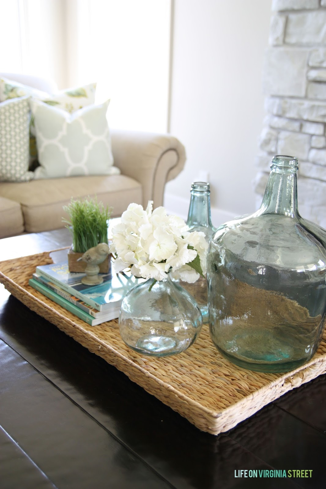 Summer decor with seagrass basket, aqua bottles and white hydrangeas