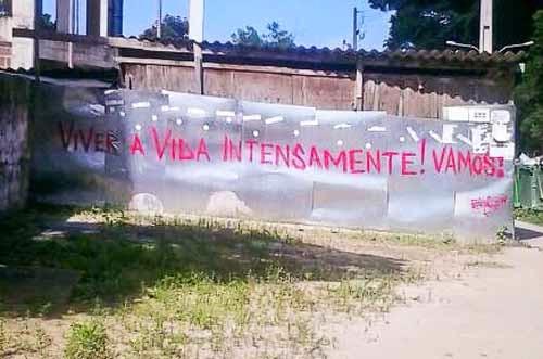 """Fotografia de um muro aonde está escrito : """"Viver a vida intensamente ! Vamos !"""""""