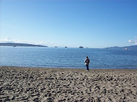 A solitary person facing the wide open waters of English Bay in Vancouver