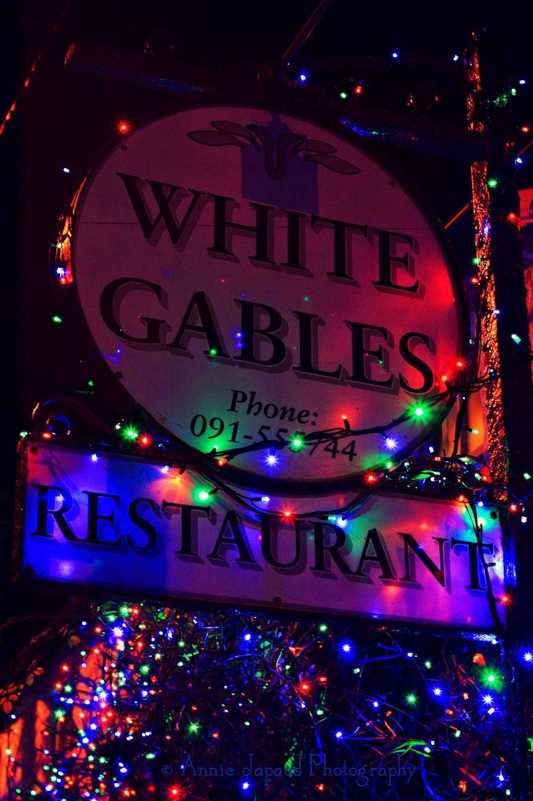 The White gables sign decorated with Christmas lights