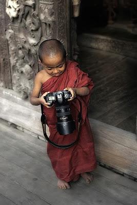 Un pequeño niño monje con su cámara Nikon en Tailandia