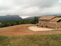 Panoràmica de La Pujada amb els cingles de Vilanova i Tavertet al seu darrere