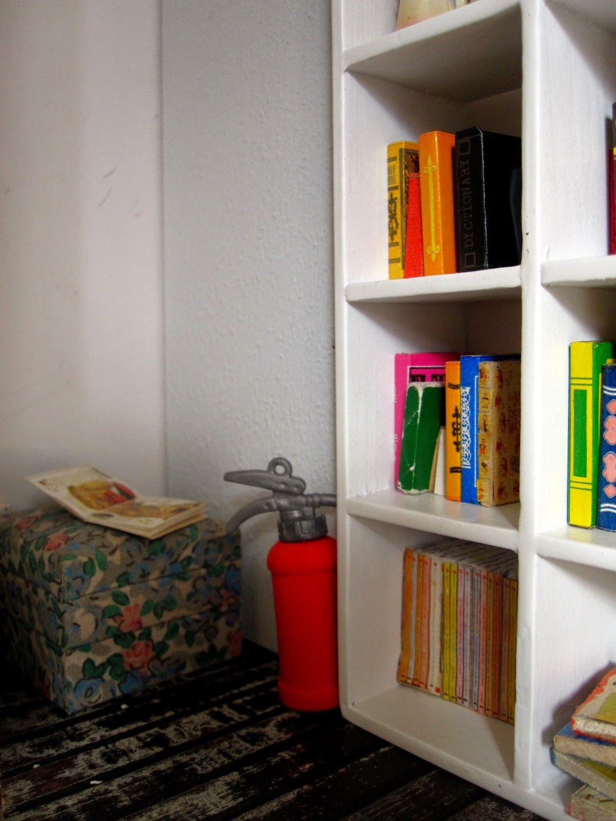Corner of a modern dolls' house miniature pop-up Little Library, with a pouffe, fire extinguisher and shelves of books.