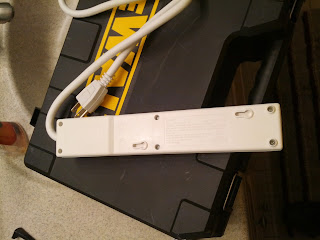 The back of the power strip, showing the two screw collars.